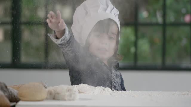 stockvideo's en b-roll-footage met een schattige aziatische jongen leert voor het koken door de voorbereiding van een bakkerij in de keuken. - schort