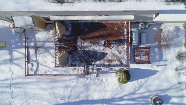 stockvideo's en b-roll-footage met een volwassen 50-jaar-oude langharige mens die een sweater draagt die vanaf een dek in een binnenplaats van het landhuis van de sneeuw na een de winters sneeuwval veegt. - 50 54 years
