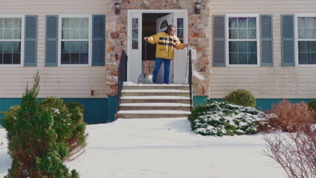 stockvideo's en b-roll-footage met een volwassen 50-jarige langharige man die een gele jas draagt die de veranda in de voortuin van het landhuis schoonmaakt van de sneeuw na een winterse sneeuwval. poconos, pennsylvania, vs - 50 54 years