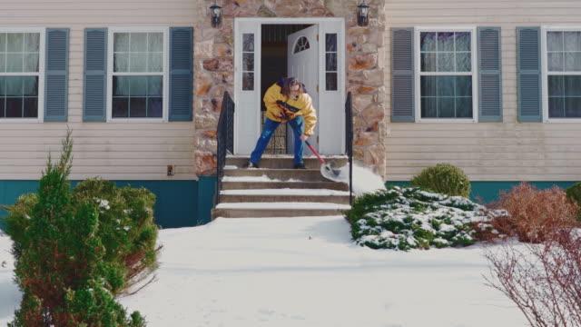 stockvideo's en b-roll-footage met een volwassen 50-jarige langharige man die een gele jas draagt die de veranda schoonmaakt en de voortuin van het landhuis van de sneeuw betrapt na een winterse sneeuwval. poconos, pennsylvania, vs - 50 54 years