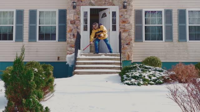 冬の降雪後、雪からカントリーハウスの前庭のポーチを掃除する黄色いジャケットを着た50歳の長髪の男性。ポコノス(アメリカ合衆国ペンシルベニア州) - 50 54 years点の映像素材/bロール