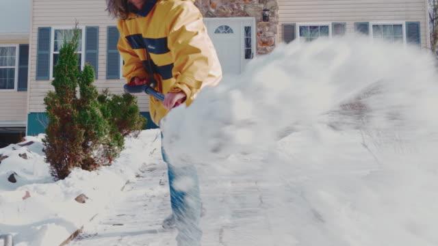 冬の降雪後、雪からカントリーハウスの前庭の道を掃除する黄色いジャケットを着た50歳の長髪の男性。ポコノス(アメリカ合衆国ペンシルベニア州) - 50 54 years点の映像素材/bロール