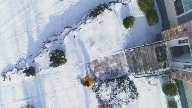 stockvideo's en b-roll-footage met een volwassen 50-jarige langharige man met een geel jasje reinigt sneeuw met een schep het pad in de voortuin van het landhuis na een winterse sneeuwval. - 50 54 years