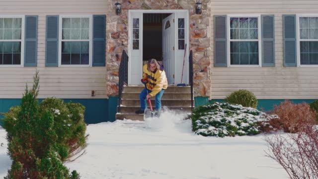 黄色いジャケットを着た50歳の大人の長髪の男性は、冬の降雪の後、カントリーハウスの前庭の道をシャベルで雪をきれいにします。ポコノス(アメリカ合衆国ペンシルベニア州) - 50 54 years点の映像素材/bロール