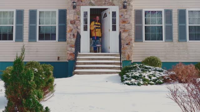 冬の降雪後、雪からカントリーハウスの入り口でポーチと階段をきれいにするために行く黄色いジャケットを着た大人の50歳の長い髪の男性。ポコノス(アメリカ合衆国ペンシルベニア州) - 50 54 years点の映像素材/bロール