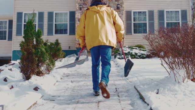 stockvideo's en b-roll-footage met een volwassen 50-jarige langharige man met een geel jasje terug naar huis nadat hij schoongemaakt pad in de voortuin van het landhuis van de sneeuw na een winterse sneeuwval. poconos, pennsylvania, de v.s. - 50 54 years