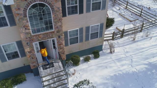 stockvideo's en b-roll-footage met een volwassen 50-jarige langharige man met een geel jasje terug naar huis nadat hij schoongemaakt pad in de voortuin van het landhuis van de sneeuw na een winterse sneeuwval. - 50 54 years