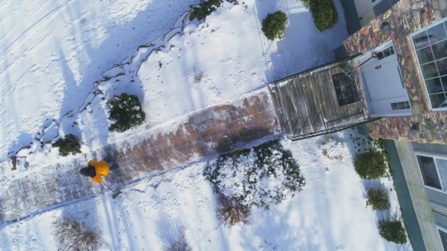 stockvideo's en b-roll-footage met een volwassen 50-jarige langharige man met een geel jasje veegt het pad, vegen weg sneeuw in de voortuin van het landhuis van de sneeuw na een winterse sneeuwval. - 50 54 years