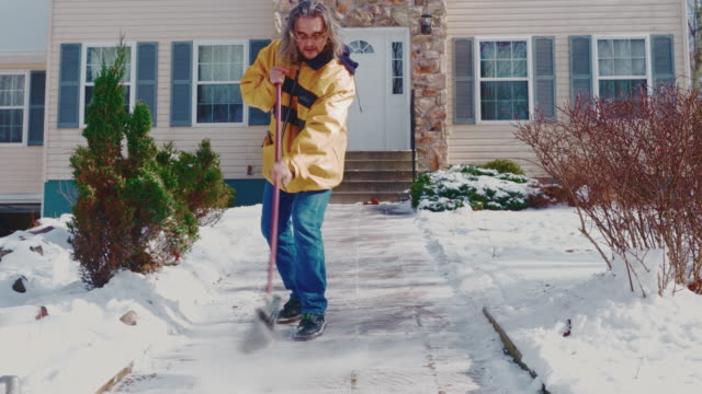 an adult 50-years-old long-haired man wearing a yellow jacket sweeps the path, sweeping away snow in the front yard of the country house from the snow after a winter snowfall. poconos, pennsylvania, usa - spade stock videos & royalty-free footage
