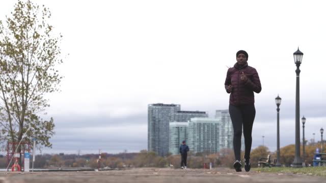 stockvideo's en b-roll-footage met een volwassen afrikaanse vrouwtje terloops uitgevoerd in de stad - fatcamera