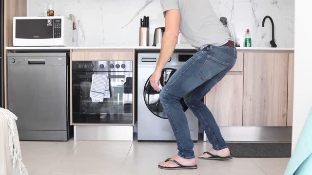 vidéos et rushes de un mâle adulte faisant la lessive dans son appartement. - un seul homme d'âge moyen
