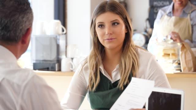 vídeos de stock, filmes e b-roll de um macho adulto fala com um barista feminino, como ele mantém-se um currículo. - barista