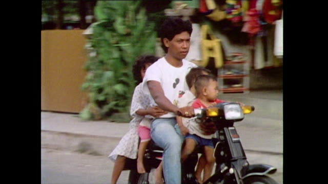 an adult man rides on a motorbike down a street in bali carrying four small children with him before arriving home 1985 - pacific islander stock videos & royalty-free footage