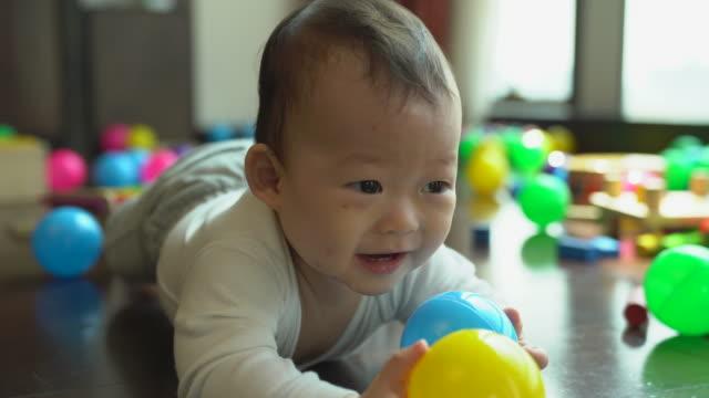 大人の視点は、自分の後ろに日光を浴びて、自分の中に這い込んでいる赤ちゃんを見ている親かもしれません。成功を目指す人類の学習の最初の概念です。赤ちゃんのかわいらしさを伝えま� - 渡す点の映像素材/bロール