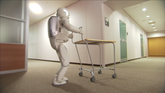 an adult-sized robot pushes a cart along an office corridor. - robot stock videos & royalty-free footage