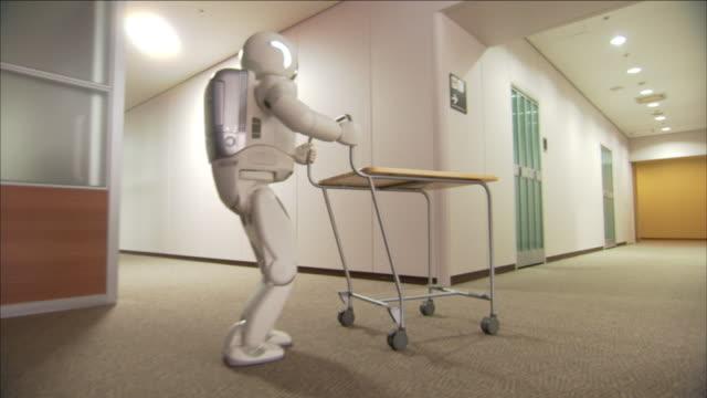 vídeos de stock, filmes e b-roll de an adult-sized robot pushes a cart along an office corridor. - robô