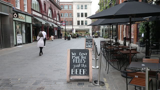 an advertisement and outdoor dining tables set up outside a restaurant at covent garden in london, u.k., on tuesday, may 11, 2021. u.k. prime... - flatten the curve stock videos & royalty-free footage