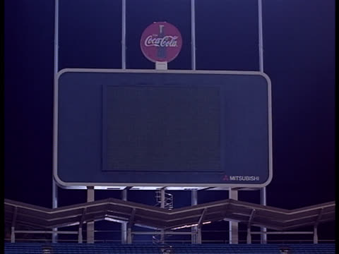 an advertisement for a soft drink stands on top of a large scoreboard. - scoreboard stock videos & royalty-free footage