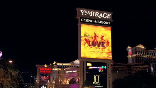 an advertisement for the beatles adorns the mirage sign in las vegas, nevada. - the beatles stock videos & royalty-free footage