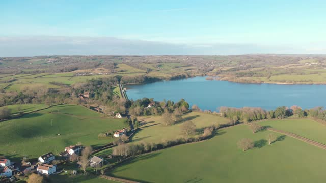an aerial drone shot of a clear blue water lake surrounded by countryside in blagdon, somerset uk - rural scene stock videos & royalty-free footage