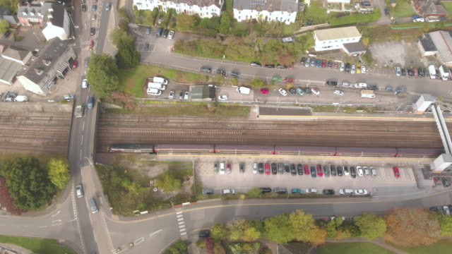 an aerial drone shot of a train leaving a station and travelling along the railway under a highway overpass in the town of totnes devon uk - city life stock videos & royalty-free footage