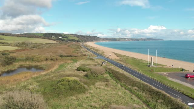 an aerial drone shot of cars driving along a long scenic highway beside slapton beach in south devon, england. - road trip stock videos & royalty-free footage