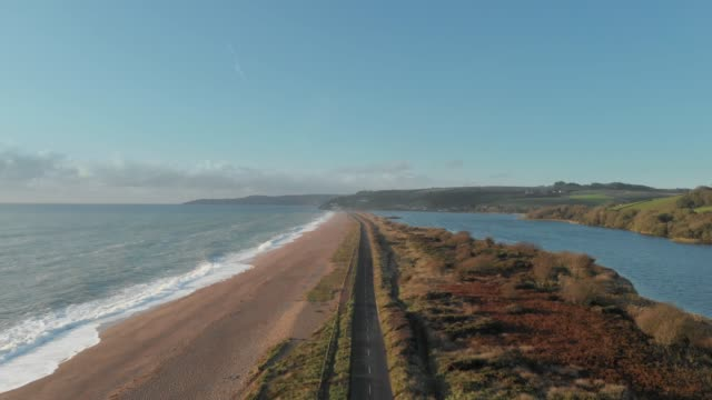 an aerial drone shot of cars driving along a long scenic highway beside slapton beach in south devon, england. - nature stock videos & royalty-free footage