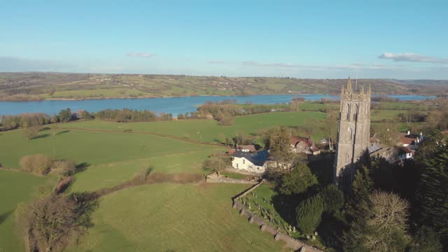 an aerial drone view of a historic church surrounded by green countryside in blagdon, somerset uk - landscape scenery stock videos & royalty-free footage