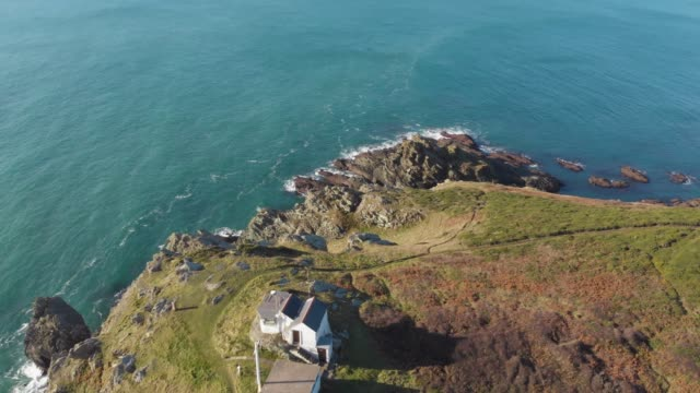 an aerial drone view of a remote house used as a lookout post on the clifftops of the south devon coast, england. - landscape scenery stock videos & royalty-free footage