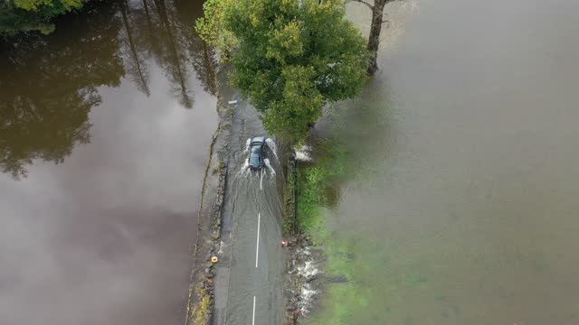 an aerial drone view of cars driving on a flooded road as the river conwy bursts its banks on october 30, 2020 in llanrwst, wales. authorities have... - road stock videos & royalty-free footage