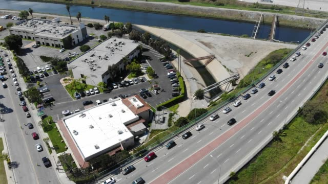 an aerial drone view of cars lined up to receive food distributed by the los angeles regional food bank amidst the coronavirus pandemic on april 18,... - line stock videos & royalty-free footage