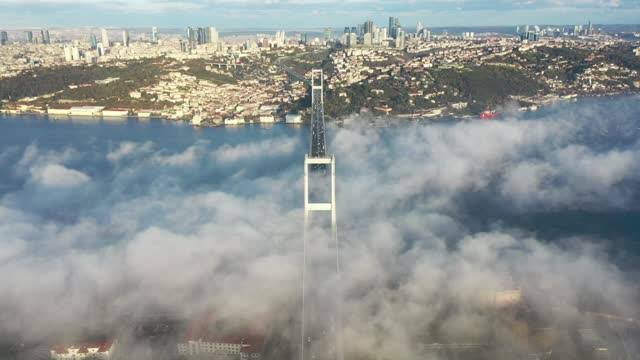 an aerial drone view of july 15 martyrs bridge mesmerizes as morning fog blanketed the bosporus strait in istanbul on tuesday . the fog covering the... - istanbul stock videos & royalty-free footage