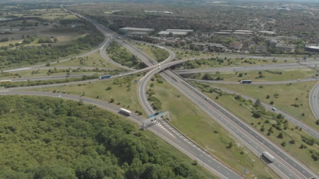 an aerial drone view of the m4 motorway flyover surrounded by green countryside, just outside bristol in england. - road junction stock videos & royalty-free footage
