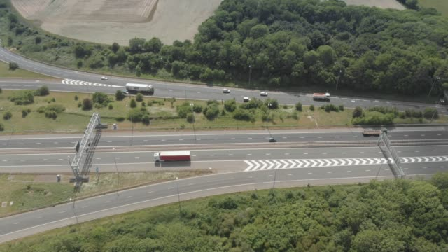an aerial drone view of the m4 motorway flyover surrounded by green countryside, just outside bristol in england, united kingdom. - motorway junction stock videos & royalty-free footage