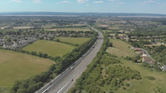 an aerial drone view of the m4 motorway surrounded by green countryside, just outside bristol in england, united kingdom. - rural scene stock videos & royalty-free footage