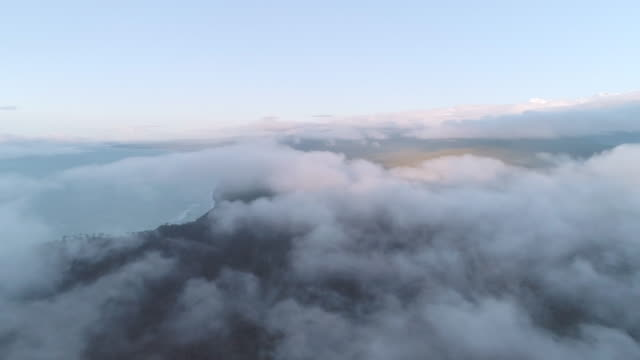 An aerial fly through the clouds looking back at Fox Glacier Mountain Range on the West Coast of New Zealand.