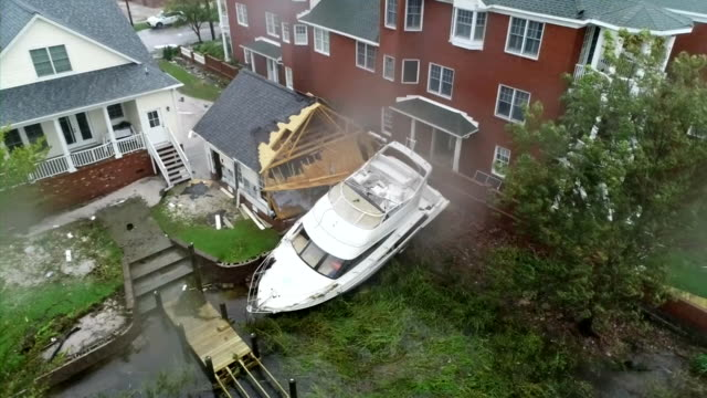 an aerial shot from a drone showing a boat crashed into the side of a home in the aftermath of hurricane florence on september 15 2018 in new bern... - aerial or drone pov or scenics or nature or cityscape stock-videos und b-roll-filmmaterial