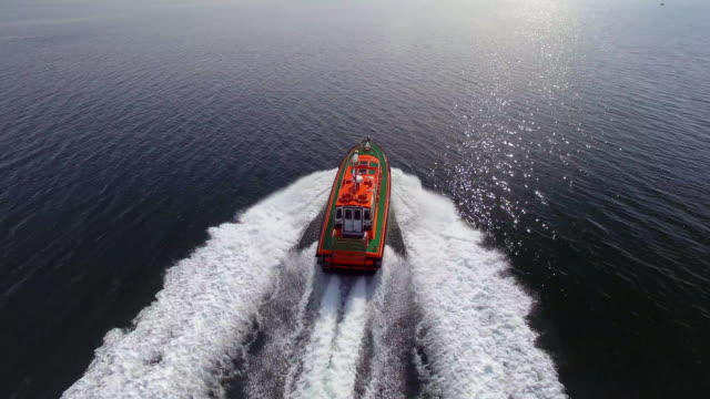 An aerial shot of a pilot boat speeding across a smooth ocean to greet its vessel to enter the shipping docklands.
