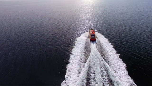 an aerial shot of a pilot boat speeding across a smooth ocean to greet its vessel to enter the shipping docklands. - david ewing stock videos & royalty-free footage