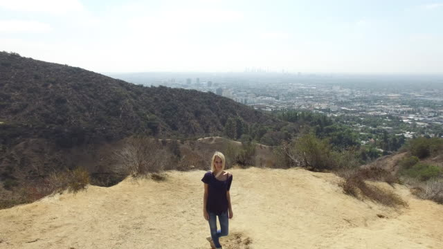 an aerial shot of a young woman standing on a hill near los angeles, in 4k - zoom ut bildbanksvideor och videomaterial från bakom kulisserna