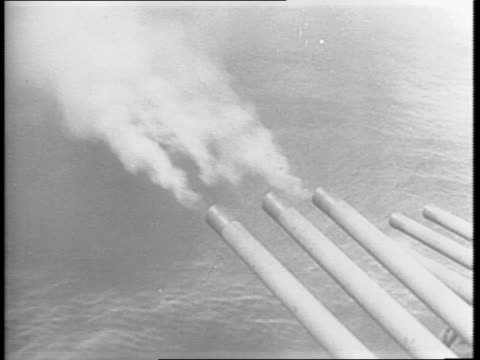 an aerial shot of marine battleships is shown sailing in the ocean / a map showing the location of guam / montage of several battle ships firing... - guam video stock e b–roll