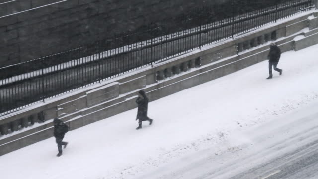 An aerial snowy blizzard New York city scene with people walking.