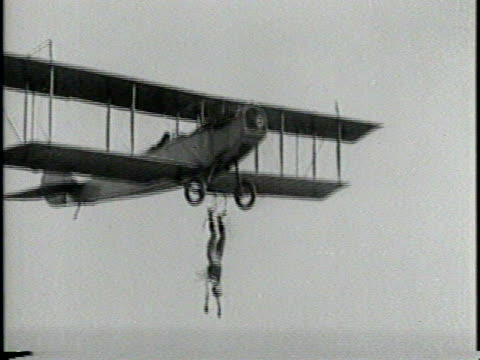 an aerial stuntman stands on the wing of a flying airplane while another airplane approaches / he jumps from the wing of the first plane to the wing... - hanging stock videos & royalty-free footage