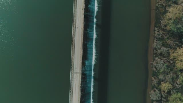 an aerial vertical 'bird's eye view' shot of a road over a dam