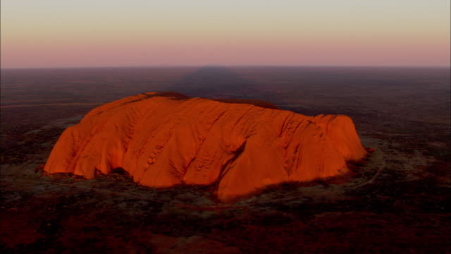 an aerial view depicts the uluru sandstone rock formation under a sunset sky.\n - エアーズロック点の映像素材/bロール