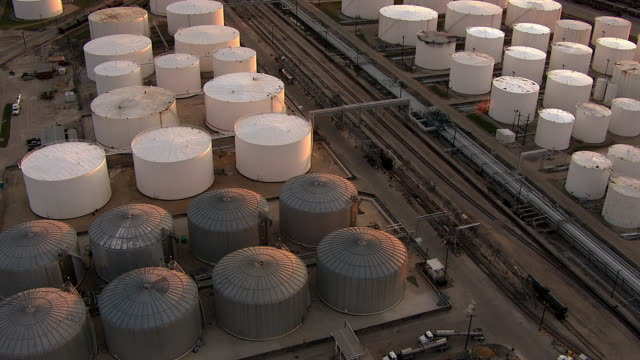 An aerial view displays rows of storage tanks at an oil refinery.