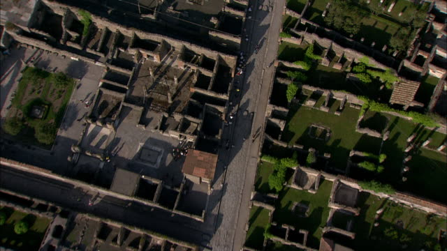 an aerial view displays the ruins of pompeii, italy. - stile classico romano video stock e b–roll