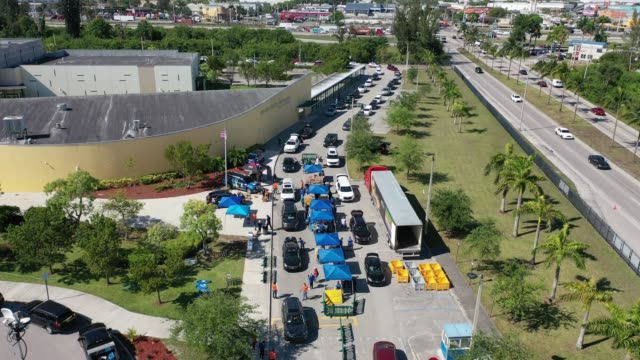 an aerial view from a drone shows city workers and volunteers as they place items of food into vehicles during a food distribution setup at hialeah... - hialeah stock videos & royalty-free footage