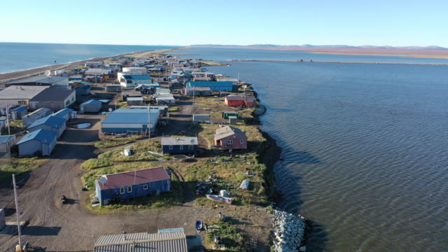 an aerial view from a drone shows kivalina which is at the very end of an eightmile barrier reef located between a lagoon and the chukchi sea on... - アラスカ点の映像素材/bロール