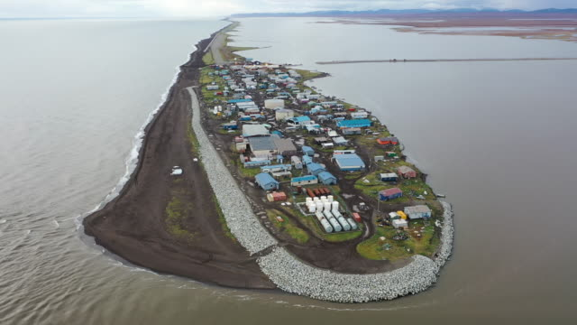 an aerial view from a drone shows kivalina, which is at the very end of an eight-mile barrier reef located between a lagoon and the chukchi sea on... - アラスカ点の映像素材/bロール